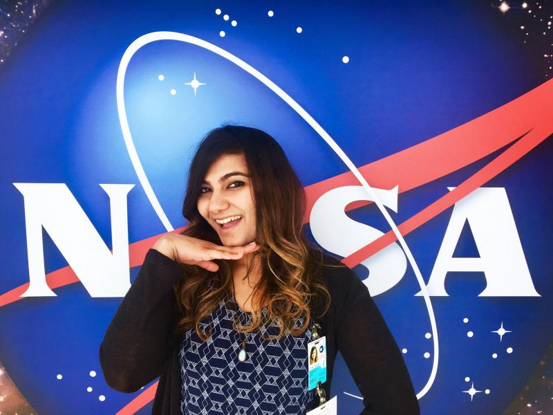 Debarati Das standing in front of the NASA meatball logo