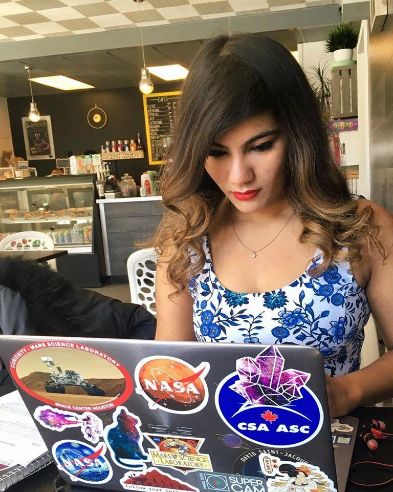 Debarati Das sitting in a cafe with stickers on her laptop
